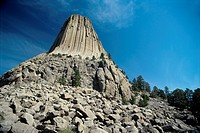 Low angle view of Devils Tower rock formation against blue sky, Wyoming, USA (thumbnail)