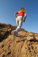Woman running up rocky trail.