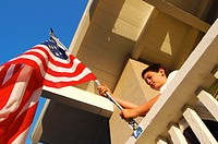 Boy raising American flag on his house