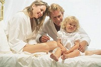Family in bed laughing