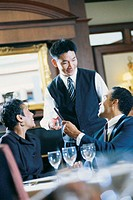 Waiter talking with couple