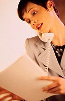 Business woman talking on telephone, reviewing paperwork