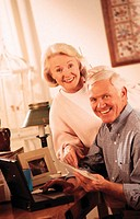 Elderly couple at laptop computer, holding bills, portrait