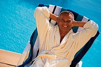 Man in robe reclining in chair at the pool, portrait