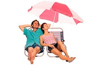 Couple sitting under beach umbrella