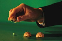 Businessman lifting chestnut shell to reveal pea.