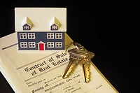 House model and house keys on top of real estate contract