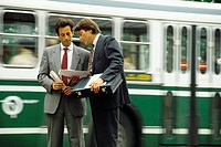 Two businessmen talking in front of bus
