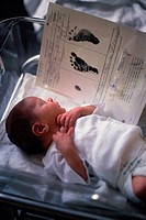 Baby in incubator with footprints sheet