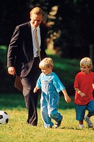 Father in business suit playing soccer with young sons