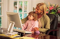 Woman working at computer with young girl sitting in her lap