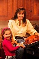 Mother and daughter taking turkey out of oven