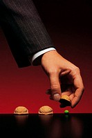Businessman lifting chestnut shells to find pea