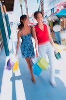 Two women walking on sidewalk with shopping bags, blurred action