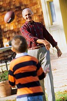 Grandfather and grandson tossing football
