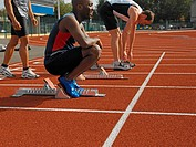 Male sprinters preparing for race