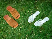 Two pairs of sandals on lawn