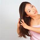 Asian woman brushing hair