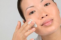 Woman applying moisturiser to cheek