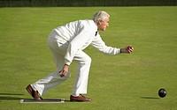 Senior Man Throwing a Bowling Ball on a Bowling Green