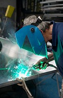 Welder Working in a Factory Wearing a Visor and Using a Welding Torch