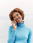 Woman Stands in a Polo-Neck Jumper Holding a Mobile Phone