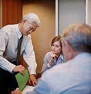 Mature Businessman Looks Through Documents on a Table While His Colleagues Watch