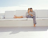 Couple Sitting on a Large White Sofa Enjoying Glasses of Wine