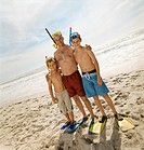Father With His Arms Around His Two Sons Standing on a Beach Wearing Swimming Flippers and Scuba Masks
