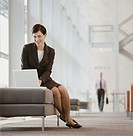 Businesswoman Sits on a Stool in a Lobby, Using a Laptop
