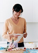 Woman Standing in a Kitchen Reading a Card