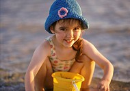 Portrait of a Young Girl Playing with a Bucket on a Beach