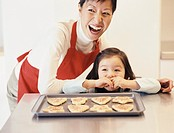 Mother Stands by a Kitchen Counter With Her Young Daughter, Laughing, the Girl Eating a Cookie From a Baking Tray