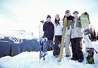 Portrait of a Mature Family of Four Standing on a Mountain Summit With Their Snowboards