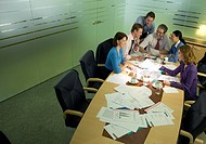 Six Businesspeople Sit at a Conference Room Table Discussing Various Documents