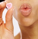Close Up of Woman Holding Heart Shaped Candy and Puckering