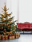 Decorated Christmas Tree With Wrapped Presents Underneath Next to a Chaise Longue