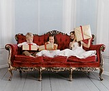 Well Dressed Young Boy and Young Girls Sit on an Ornate Sofa Excitedly Unwrapping Gifts