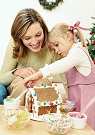 Mother and Daughter Decorating a Chocolate House with Candy