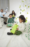 Four Young Children Sitting in a Living Room Unwrapping Christmas Presents