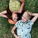 Teenage Girls Face to Face Lying on Grass