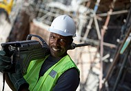 Portrait of a Male Builder in a Hard Hat, Carrying a Drill on His Shoulder