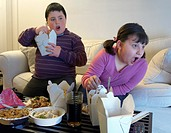 Overweight Brother and Sister Sitting Side by Side on a Sofa Eating Takeaway Food and Watching the TV With Amazement