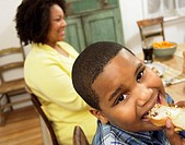 Close-Up of a Young Boy Sitting at the Table With His Mother, Eating a Slice of Bread