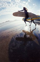 Fisheye Lens Shot of Two Surfers Running Across a Beach, in Silhouette