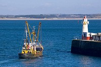 UK, GB, England, Cornwall, fishing boat setting off for sea past newlyn lighthouse