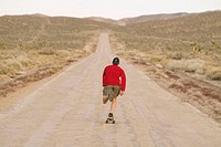 A man skateboarding on a desert road near Lone Pine, California. USA