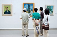 Visitors watching 'Road with Cypress and Star' (1890) painting by Vincent Van Gogh in Kröller-Müller Museum, Het Nationale Park De Hoge Veluwe. Gelder...