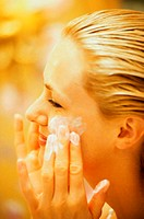 Close-up of a young woman applying moisturizer on her face