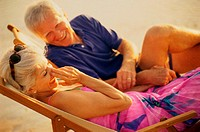 Senior couple sitting on beach chairs